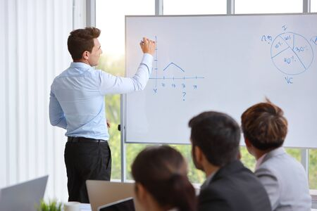 businessman coaching in team meeting or training, speaker drawing graph on white board (business seminar concept)