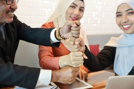 businessman and businesswoman muslim meeting and stacking hands (partner or success business concept) Stock Photo
