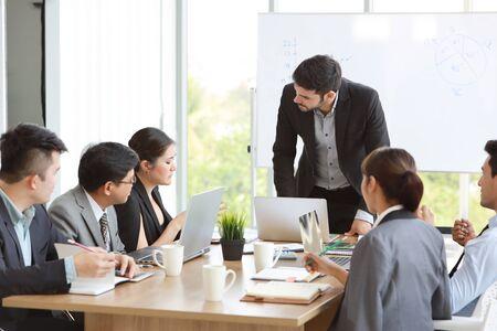 Kaukasischer Dozent, der eine öffentliche Präsentation mit dem Ergebnis des Unternehmensgeschäftsdiagramms auf dem Whiteboard im Besprechungsraum hält, und multiethnische Geschäftsleute achten darauf (Schulungs- oder Seminarkonzept)