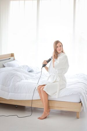 young beautiful woman using a hair straightener and smiling in bedroom in the morning Фото со стока