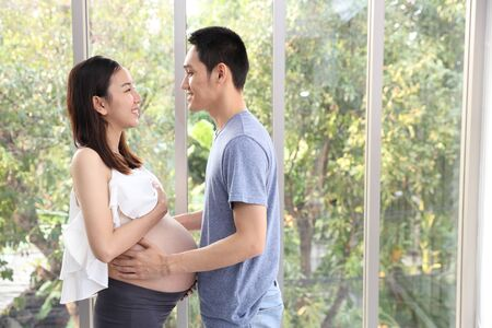 young asian husband standing and embracing young pregnant belly wife beautiful green trees background (happy family or couple concept)