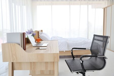 working desk with computer, cell phone and a cup of coffee in white bed room with bed
