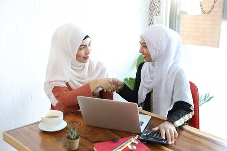 new generation businesswoman muslim people shaking hands after finished business deal in coffee shop with computer and coffee cup on wood desk