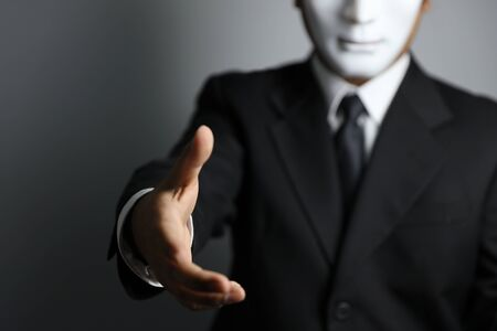 politician or businessman wearing black suit and white mask shaking hand