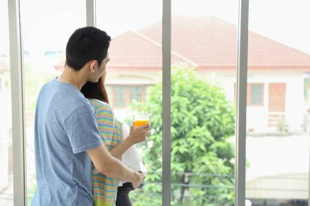 back view image of young asian husband embracing young asian pregnant belly wife and looking at something through the window with happiness and smile while her holding orange juice