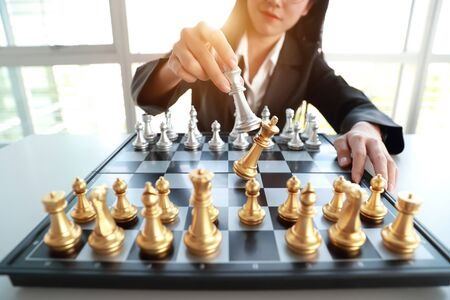 Businesswoman playing chess board game idea of management strategy and leadership concept