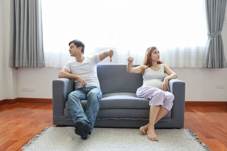 full shot of asian pregnant wife and caucasian husband sitting on sofa in living room with angry motion and showing thumb down or dislike something with unhappy face