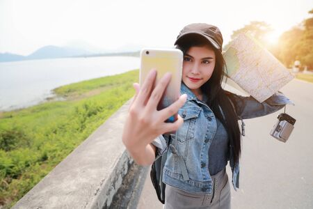 Young asian traveler using smart phone and do self portrait while traveling during holiday vacation