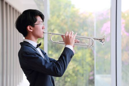 young musician man wearing black suit playing trumpet