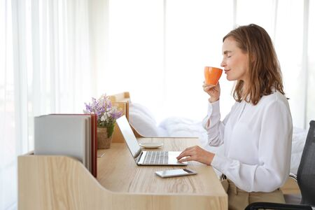 beautiful girl drinking a cup of coffee or tea in the morning with laptop computer and cell phone on wood table in bedroom