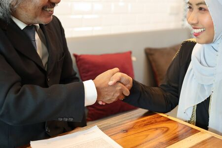 businessman and businesswoman muslim people shaking hands after finished business deal in coffee shop with computer and coffee cup on wood desk