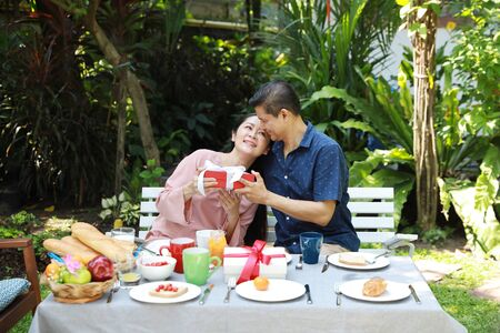 asian elderly couple with blue and pink shirt sitting at a breakfast table in backyard outdoor on wedding anniversary day. Asian elder husband giving gifts to his asian elder wife with smiling face.