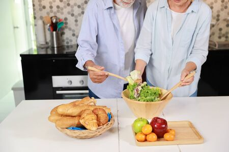 close up caucasian elderly wife making salad in the kitchen with her elderly husband happily during his retirement life on table with fruits in happy holiday