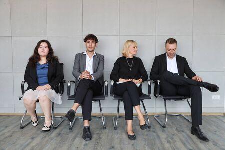 portret wieloetnicznych ludzi biznesu w strojach roboczych, którzy siedzą i ustawiają się w kolejce do rozmowy HR