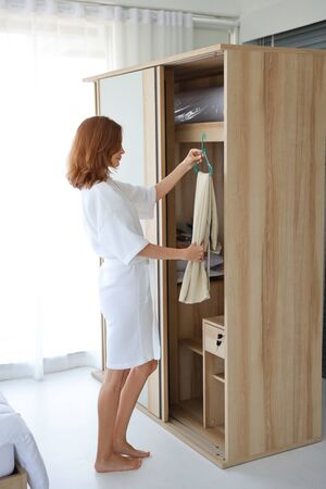 young cheerful caucasian woman in white pajama choosing clothes in wardrobe in bedroom with happy face (life style and relaxation concept)