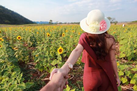 a couple holding hand on among sunflower field in nature Stock Photo