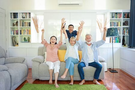 Happy elder multiethnic family sitting on grey sofa in living room and they raise their hands while watching football and their team got winner with smiling face Stock Photo