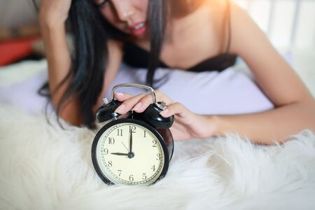 young woman depressed and stressed with alarm clock from wake up late