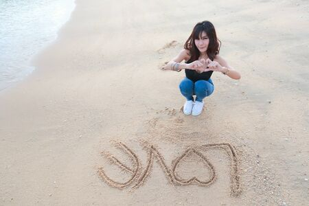 portrait of beautiful woman doing heart symbol on hands with love word on sand Stock Photo