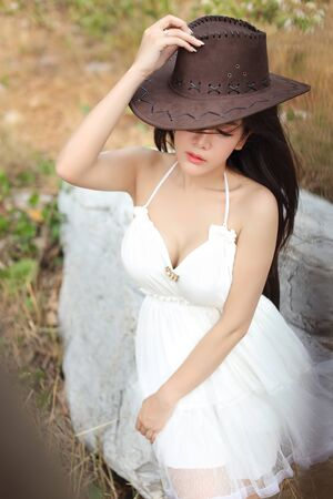 cute and beautiful girl in white dress sitting in nature outdoors with hat and close her eyes