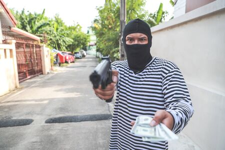 thief stealing money with gun in his hand (theft concept) Фото со стока