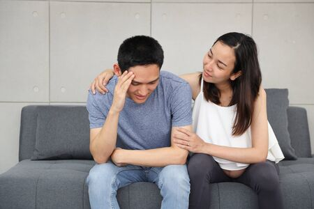 young pregnant wife comforting and touching shoulder young husband while sitting on sofa