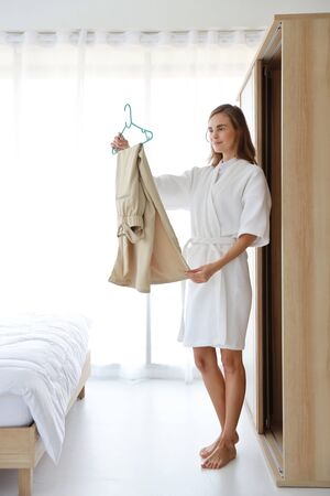 Full length shot of young cheerful caucasian woman in white pajama choosing clothes in wardrobe in bedroom with happy face (life style and relaxation concept) Stockfoto