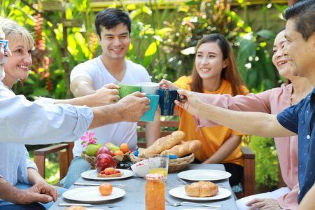 Felice famiglia multietnica seduta a un tavolo per la colazione nel cortile all'aperto in una giornata di sole con una faccia sorridente mentre tutti fanno clic sugli occhiali.