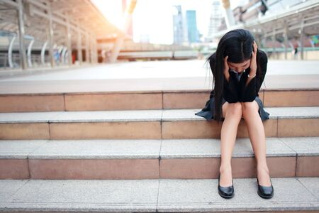 unemployed businesswoman got stress from loss job and sitting on stair in city while other people go to work Stock Photo