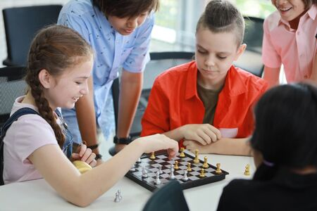 cute and smart kids playing chess in class (education concept) Stock Photo