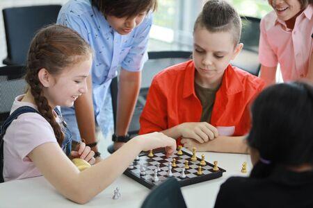 Niños lindos e inteligentes jugando al ajedrez en clase (concepto de educación) Foto de archivo