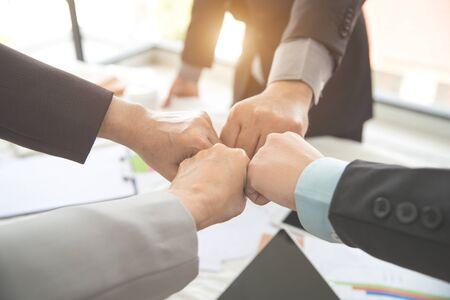 Geschäftsleute, die während des Meetings den ersten Stoß nach abgeschlossenem Projekt geben, als Hintergrund (Konzept von Teamarbeit und Partnerschaft)