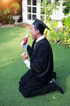 Happy man graduated holding and showing degree, idea for education concept