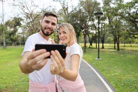 young caucasian couple in love using cell phone portrait themself in the park (relaxation with technology concept)