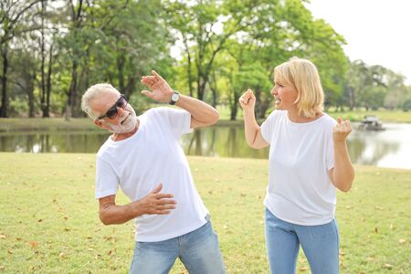 elderly wife is angry and husband is shocked at the same time in park with green trees during summer time Archivio Fotografico - 130891019