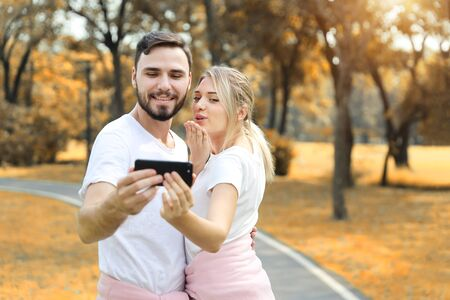 young couple in love using cell phone together and giving kiss to smart phone in the park (vacation or technology concept)
