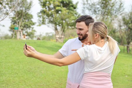 young couple in love using cell phone together and pointing to cell phone in the park (relaxation or technology concept) Stock Photo