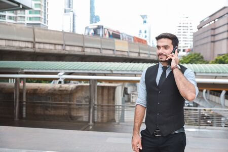 side view successful caucasian businessman in black suite who standing in downtown, he using cell phone with happy smiling face with city and skytrain background
