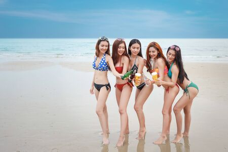 group of happy and sexy asian friends who wearing bikini and swiming suit. they drinking and cheering with alcohol and soft drink bottle on sandy beach party. young people having fun and happiness face. Standard-Bild