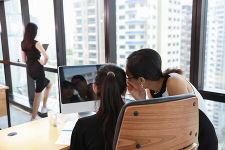 two asian colleagues businesswomen whispering or gossiping something about her boss who standing and working on computer