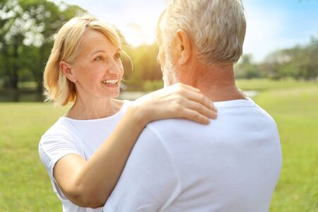 smiling elderly couple with white shirt and blue jean embracing in park in autumn time with sun light effect Standard-Bild