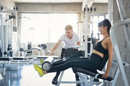 sporty caucasian fitness woman using exercise machine with trainer Stok Fotoğraf - 133995124