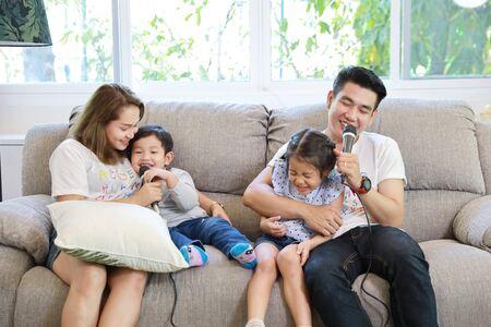 Gelukkige Aziatische familie, vader, moeder dochter en zoon zingen karaoke op de bank in de woonkamer met een blij lachend gezicht (ontspanning en technologie concept)