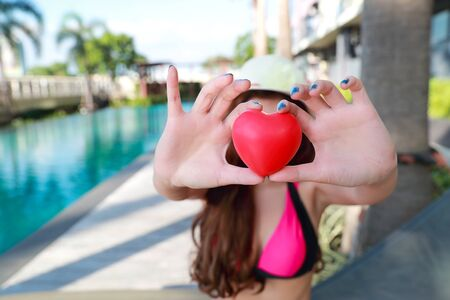 young and sexy girl giving heart symbol near swimming pool