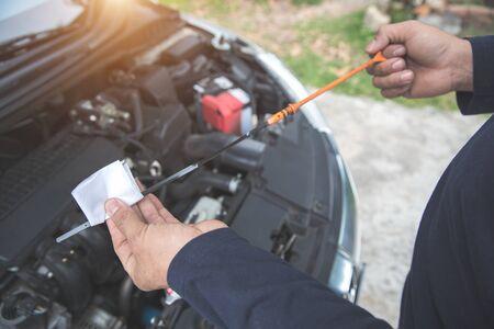 Le mani del meccanico controllano il livello dell'olio