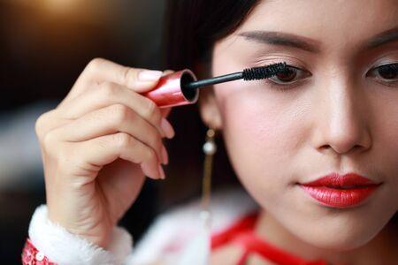 young asian santa girl applying eye shadow on beautiful face Stok Fotoğraf