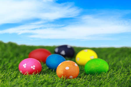 Group colorful and decorated beautiful easter eggs on green grass in nature with blue sky background. Advertising image Easter festival concept with free space.