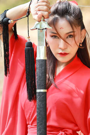 Young beautiful asian woman dressing in traditional Chinese old fashion warrior style with ancient word. Full length cute girl in red dress looking at camera in nature outdoor. Travel in Asia concept