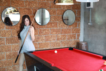 beautiful and asian woman in grey dress playing billiard or snooker on red pool table with happy smiling face during holiday vacation