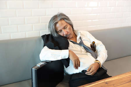 senior businessman with suit who holding empty alcohol bottle and sleep on sofa in coffee shop (stress or failure in business concept)